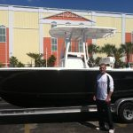 Man standing next to boat on a trailer